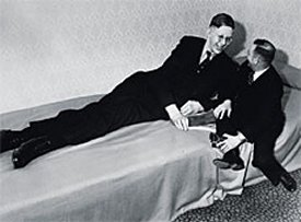robert-wadlow-sleeping-in-bed-and-a-short-man-sitting-near-him
