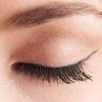 close up of womans brown eye lid with false eye lashes